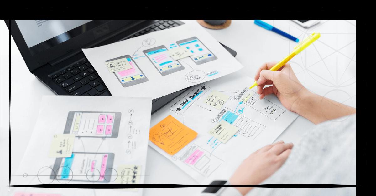 B! Das Bild zeigt einen weissen Schreibtisch mit einem schwarzen Laptop und drei A4-Blätter, auf welchen Tablets gezeichnet sind, die verschiedene Designs und Navigationselemente als Entwürfe enthalten. Es sind nur die beiden Hände der zeichnenden Frau zu sehen.