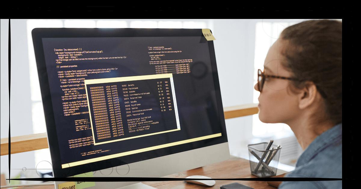 B! Das Bild zeigt eine Frau mit Brille vor einem iMac sitzend. Auf dem Bildschirm ist eine Programmiersprache zu sehen.